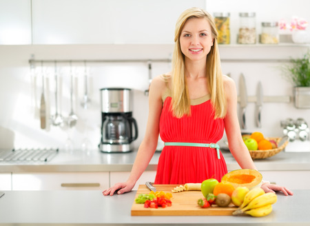 Portrait of happy young woman cutting fruits in kitchen photo