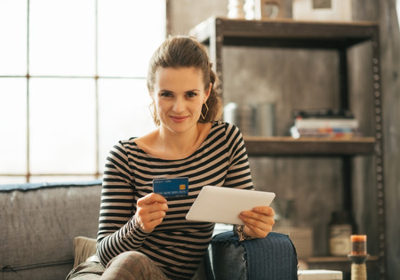 topicality: Portrait of happy young woman with credit card and tablet pc Stock Photo