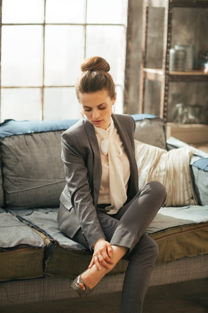 Thoughtful business woman in loft apartment checking tired legs