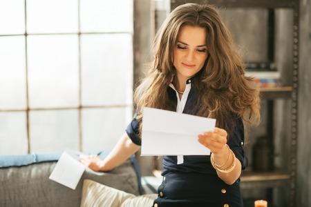 로프트 아파트에서 젊은 여자 독서 편지 쓰기