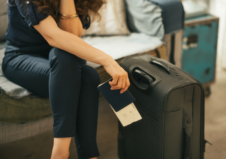 Closeup on young woman with passport, ticket and luggage