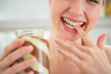 licking finger: Closeup on happy young woman licking chocolate butter from finger Stock Photo