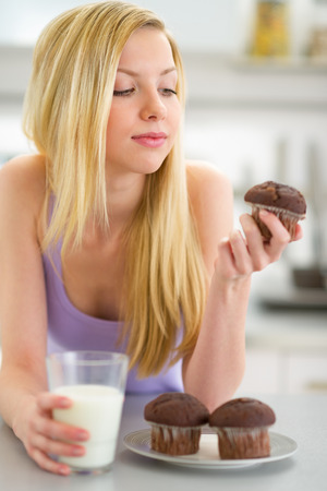 Teenager girl eating muffin with milk in kitchen photo