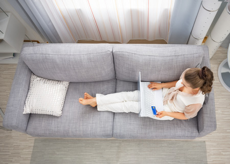 divan sofa: Young housewife laying on sofa in living room and making online shopping