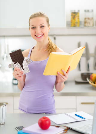 classbook: Happy teenager girl reading book and eating chocolate Stock Photo