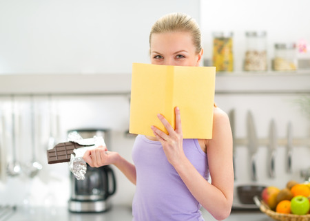classbook: Teenager girl with chocolate reading book Stock Photo