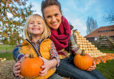Portrait of smiling mother and child sitting on haystack with pumpkins Фото со стока