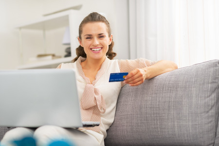 card making: Happy young housewife with credit card making online shopping Stock Photo