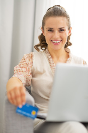 topicality: Portrait of happy young housewife with laptop holding credit card
