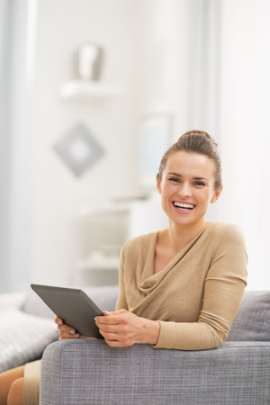 topicality: Portrait of happy young woman with tablet pc in living room Stock Photo