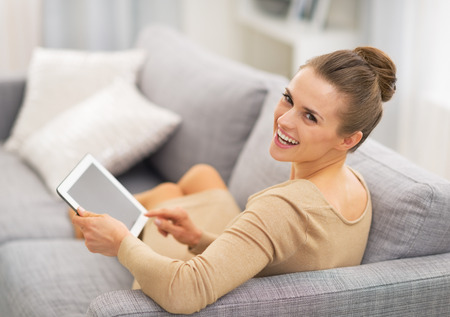 Portrait of happy young woman sitting on sofa and using tablet pc