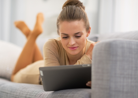 topicality: Young woman laying on couch and using tablet pc Stock Photo