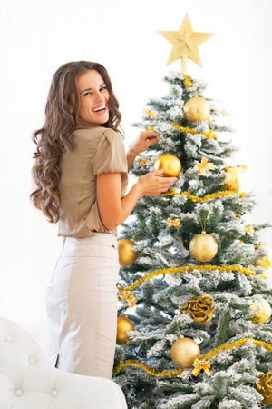 Portrait of smiling young woman decorating christmas tree Stock Photo
