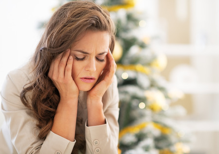 holiday stress: Portrait of stressed young woman near christmas tree