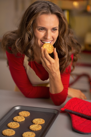 Young housewife eating fresh christmas cookies photo