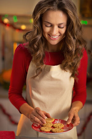 Portrait of happy young housewife with christmas cookies in kitchen photo