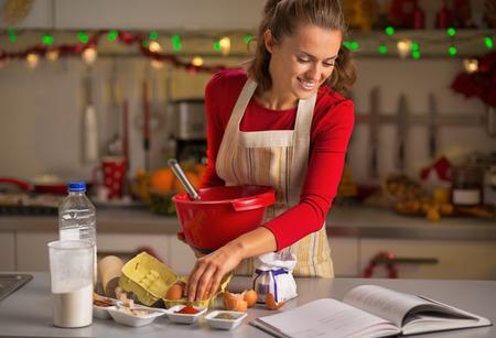cocinando: Joven ama de casa feliz que hace las galletas de navidad en la cocina Foto de archivo