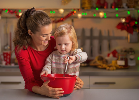 whisking: Happy mother and baby whisking dough in christmas decorated kitchen
