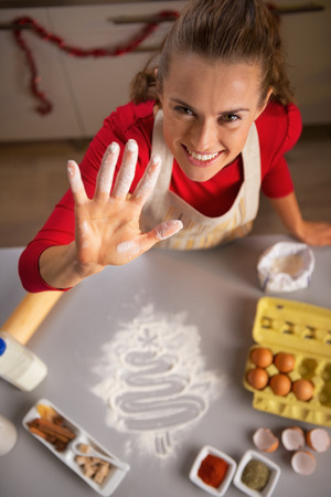 smeared: Young housewife showing hand smeared in flour