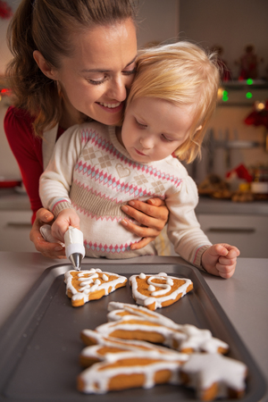 Portrait of happy mother and baby making christmas cookies in kitchen photo
