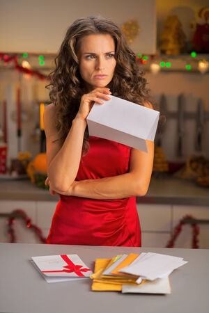 disquieted: Concerned young housewife holding letter in christmas decorated kitchen Stock Photo