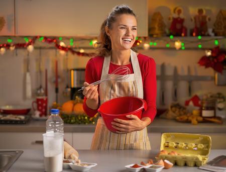 batidora: Ama de casa joven feliz batiendo masa en navidad decorado cocina Foto de archivo