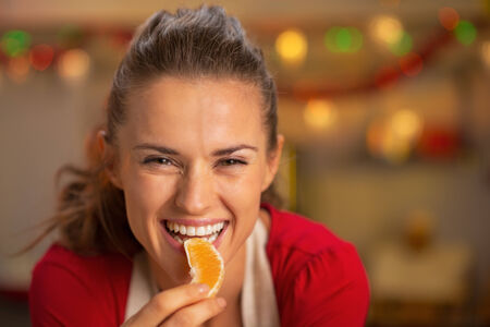 modern lifestyle: Portrait of young housewife eating orange in christmas decorated kitchen