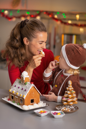 Happy mother and baby eating cookie in christmas decorated kitchen photo