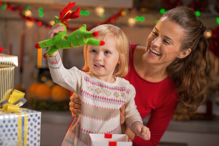 Portrait of happy mother and baby playing in christmas decorated kitchen photo