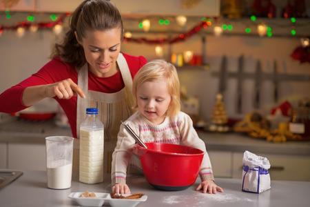 galletas de navidad: Feliz madre y el bebé que hacen las galletas de Navidad en la cocina
