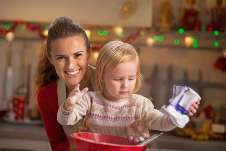 christmas baby: Portrait of flour smeared mother and baby making christmas cookies