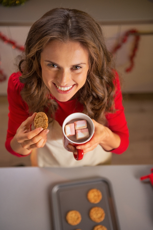 Happy young housewife eating homemade christmas cookies with cup of hot chocolate photo