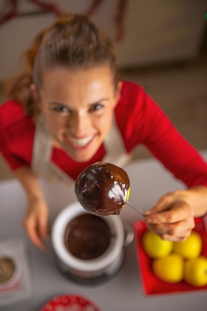 Closeup on happy young housewife showing homemade apple in chocolate glaze photo