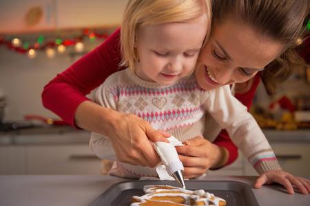 baking christmas cookies: Portrait of happy mother and baby making christmas cookies in kitchen