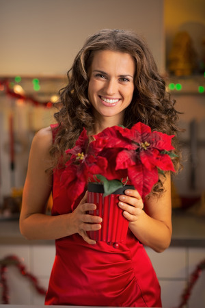 Portrait of happy young woman holding christmas rose photo