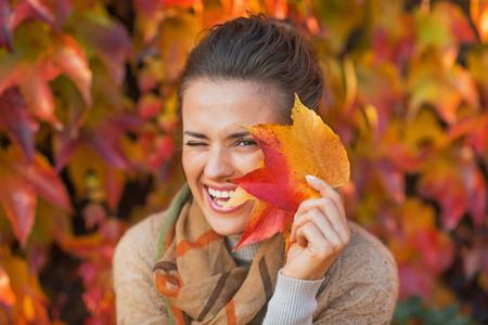 Portret van gelukkige jonge vrouw zich te verschuilen achter de herfst bladeren in de voorkant van het gebladerte