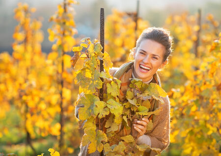 Portrait of happy young woman in autumn vineyard looking out from branch photo