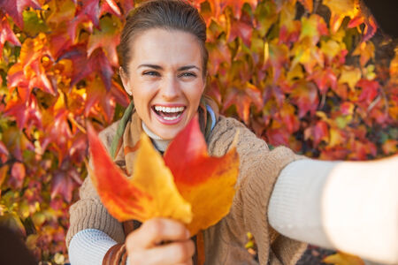 young leaves: Smiling young woman with autumn leaf making selfie