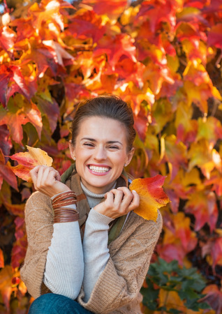 Portrait of smiling young woman in front of autumn foliage Stok Fotoğraf