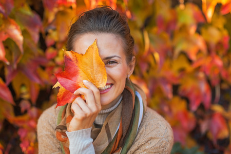 Portret van gelukkige jonge vrouw zich te verschuilen achter de herfst bladeren in de voorkant van het gebladerte Stockfoto - 35297506