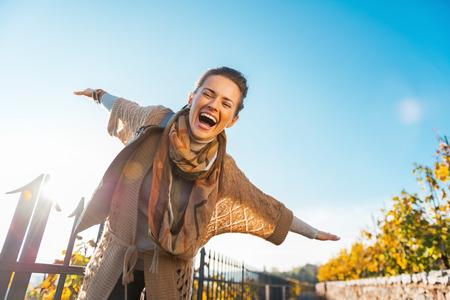 Mujer joven feliz que tiene tiempo de diversión en otoño al aire libre