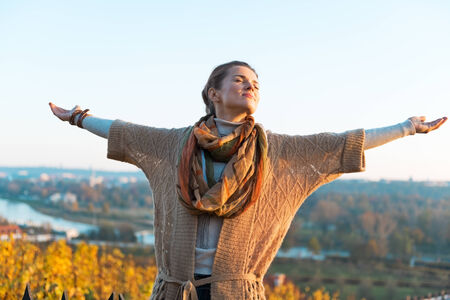 rejoicing: Happy young woman in autumn outdoors in evening rejoicing Stock Photo