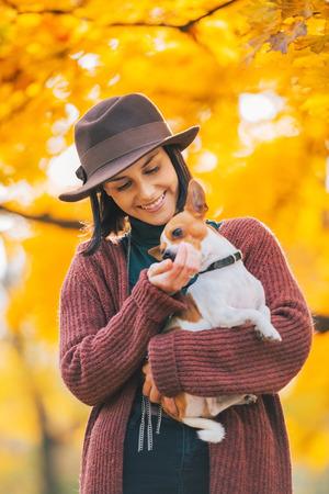 Gelukkige jonge vrouw hond in openlucht in de herfst