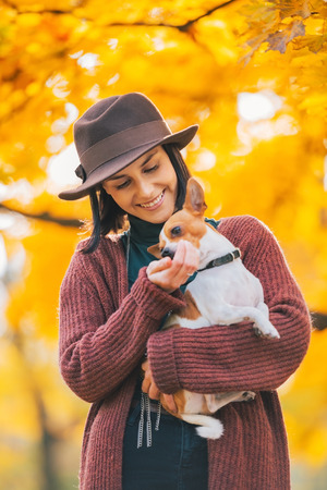 Happy young woman dog outdoors in autumn
