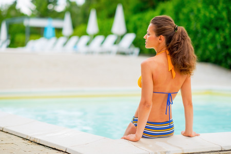 poolside: Young woman sitting at poolside. rear view