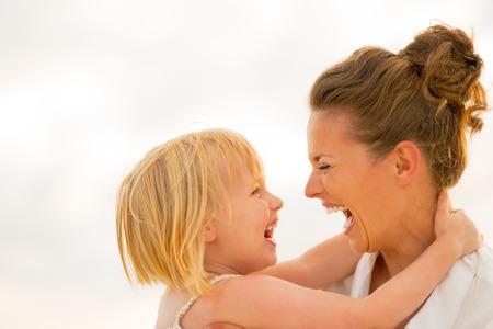 Retrato de reír a la madre y del bebé que abraza en la playa en la noche