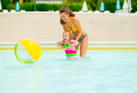beachball: Happy mother and baby girl playing with beach ball in pool