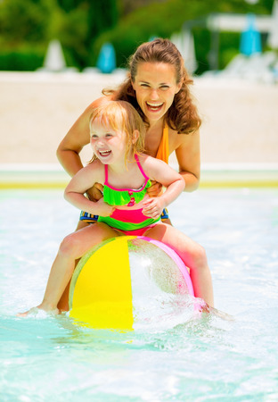 beachball: Portrait of happy mother and baby girl playing with beach ball in pool