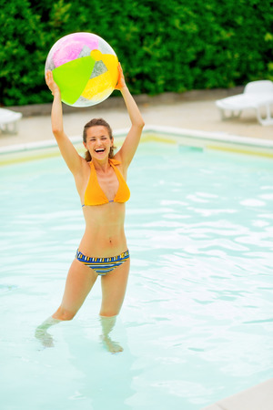 beachball: Full length portrait of smiling young woman with beach ball in pool