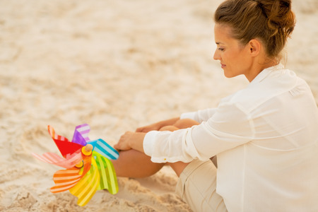 anonym: Young woman with colorful windmill toy sitting on beach at the evening. rear view